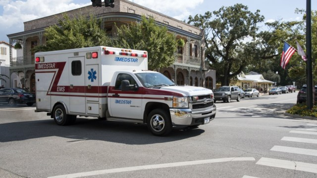 An ambulance on an emergency call driving through the town center of Fairhope