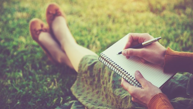 woman sitting in grass writing in journal