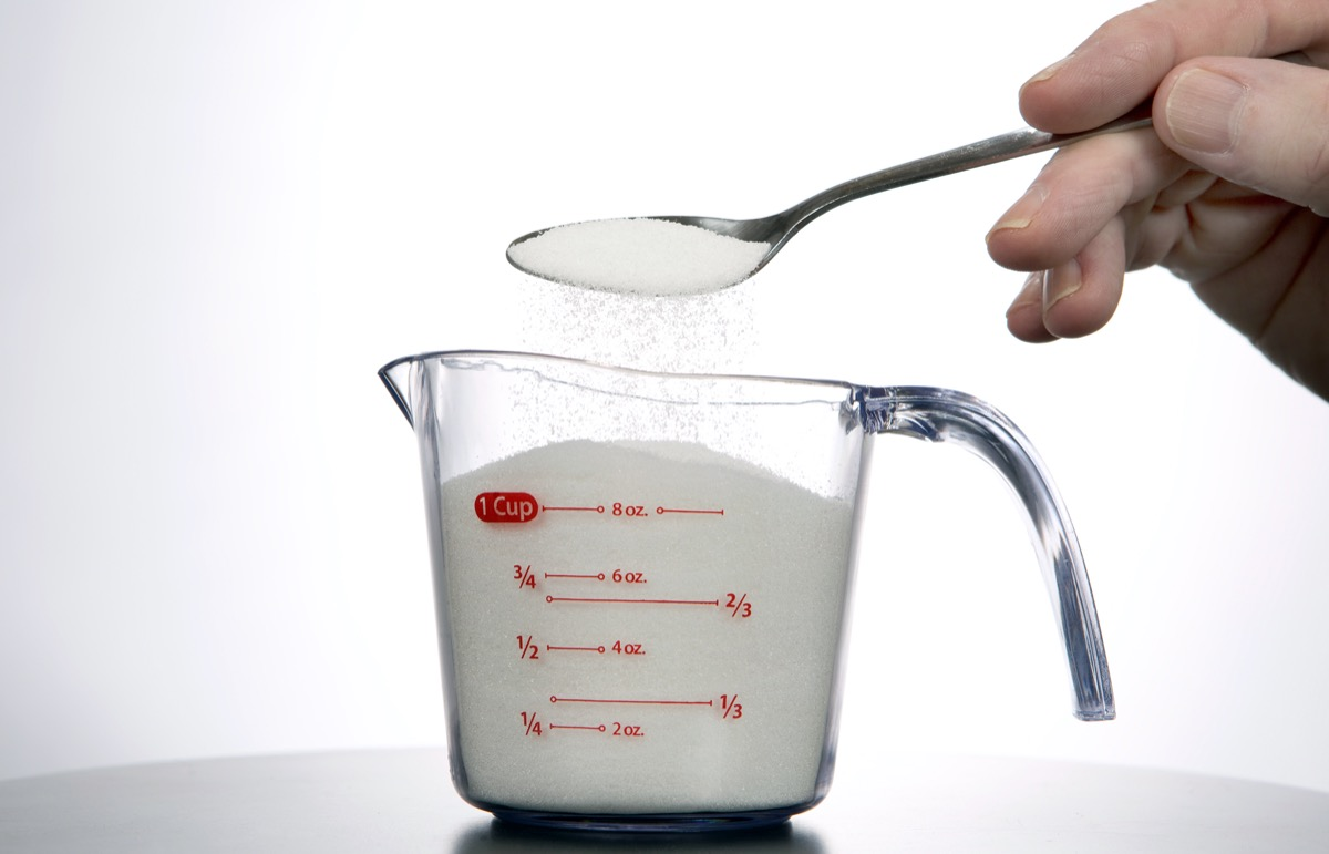 Man pours a spoonful of sugar into a measuring cup.