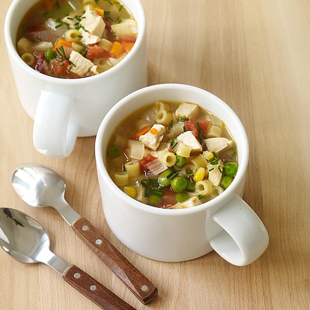 chicken noodle soup in two white mugs
