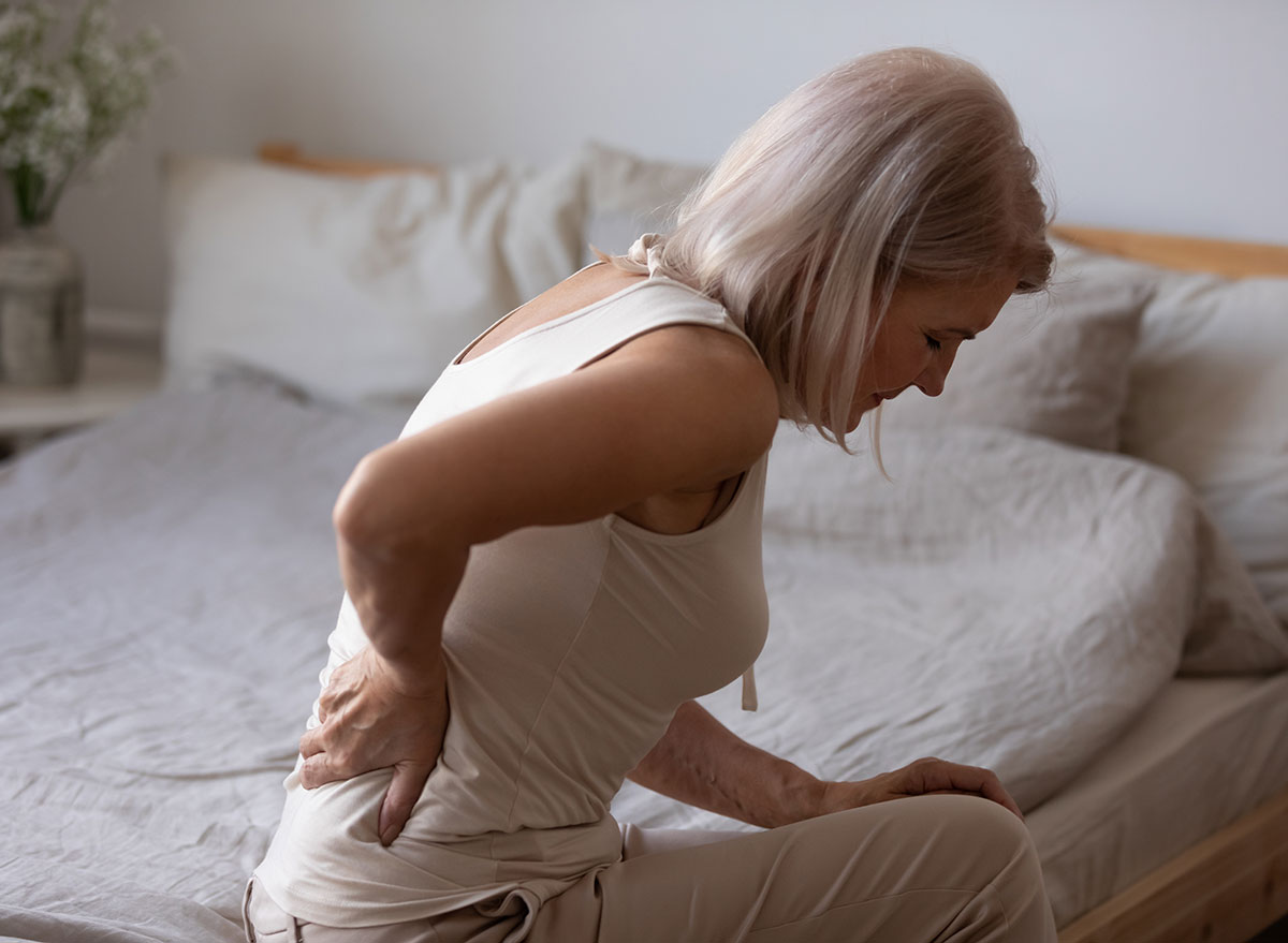 woman with back pain sitting on bed