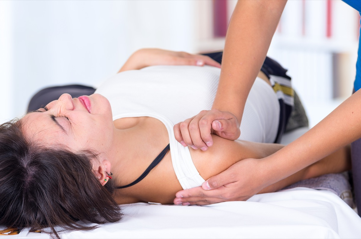 Wwoman in pain lying while getting a massage from specialist