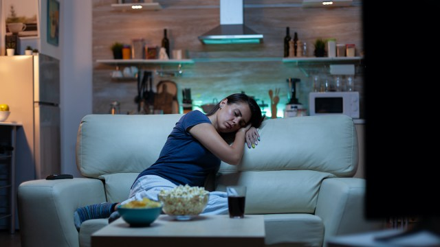 Woman falling asleep on sofa in front TV. Tired exhausted lonely sleepy lady in pajamas sleeping in front of television sitting on cozy couch in living room, closing eyes while watching movie at night