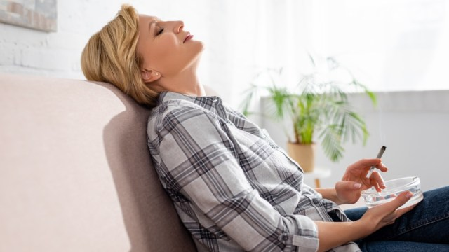 A mature woman with closed eyes sitting on sofa and holding joint with legal marijuana.