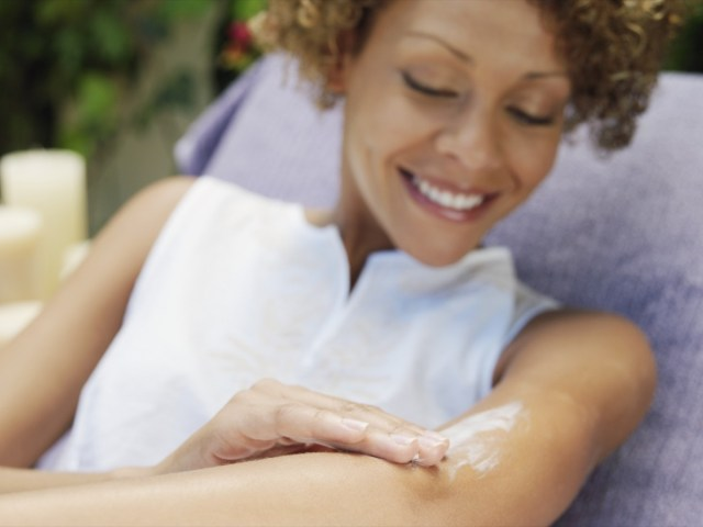 happy woman relaxing in the garden smiling as she applies sunscreen or skin cream