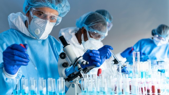 Virus experts are working using microscope in laboratory with protective suit, gloves glasses and mask