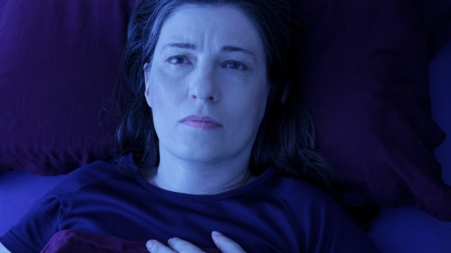 Middle aged woman lying awake in her bed at night, worrying because of an uncomfortable pressure in her chest and an irregular heartbeat