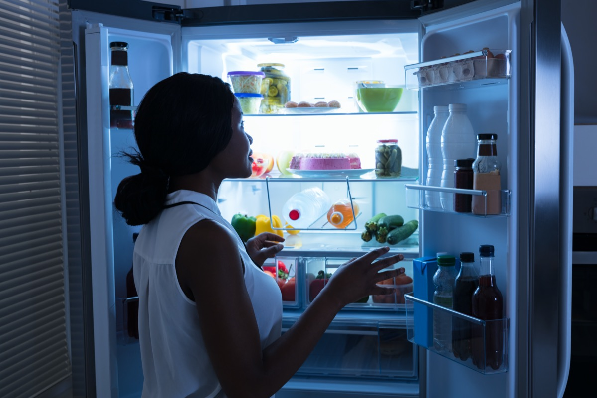 Woman Taking Out Bottle From Open Refrigerator