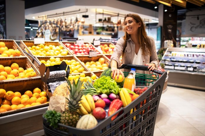 young woman buying lots of fruit