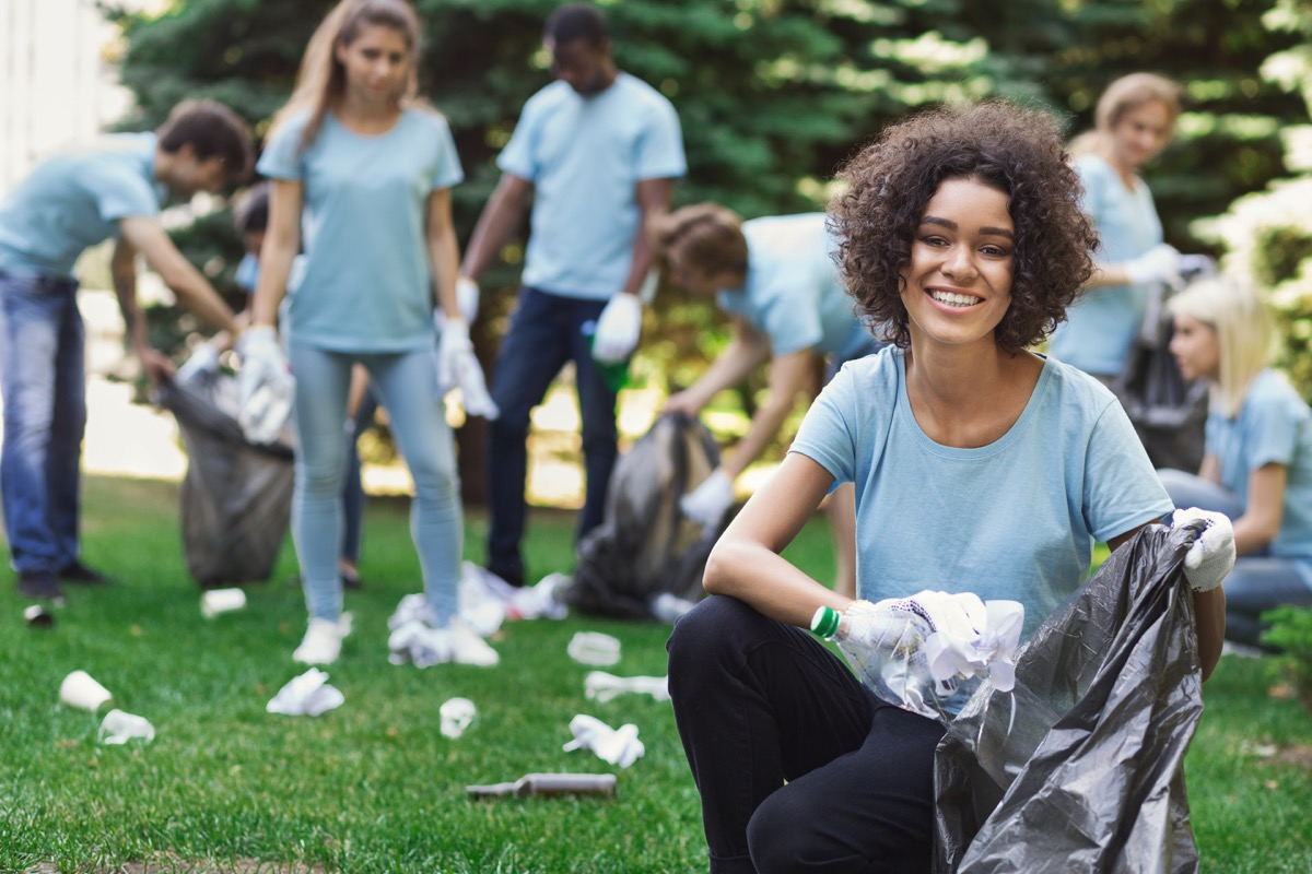 Happy woman and group of volunteers with garbage bags cleaning area in park, copy space