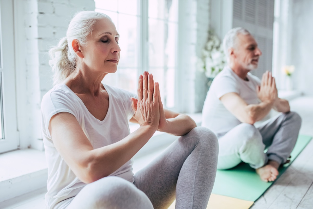 Senior couple is doing fitness training at home.