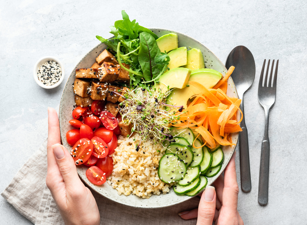 healthy vegetable plant based bowl tomatoes carrots avocado brown rice cucumbers leafy greens