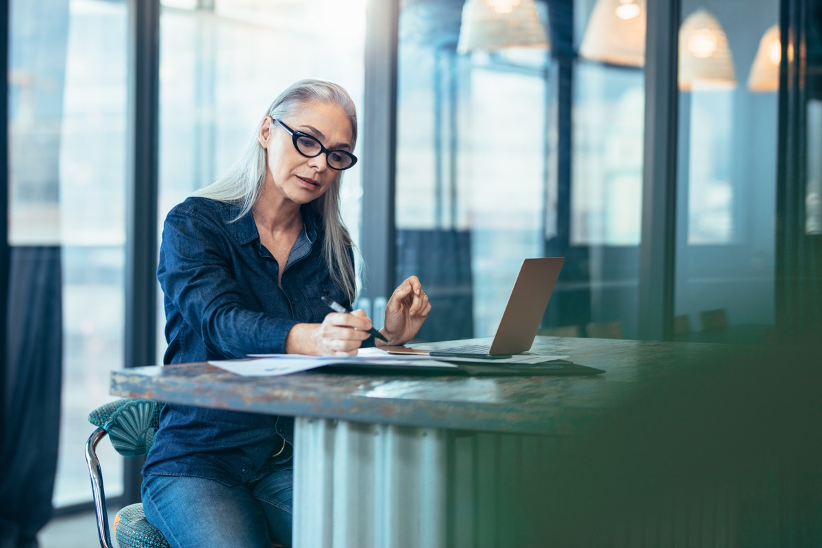 senior woman sitting at table in office and